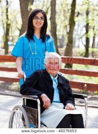 Walking With Senior Patient In Wheelchair