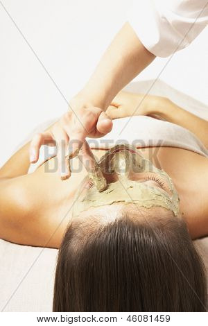 Woman applying mask to woman's face