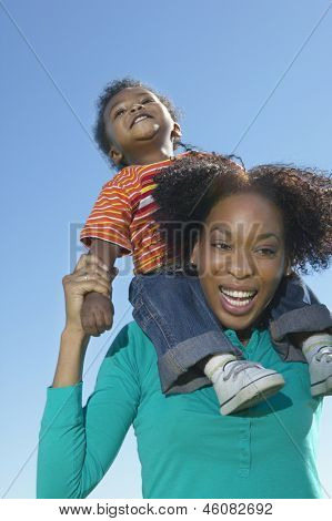 Low angle view of woman with little son on shoulders