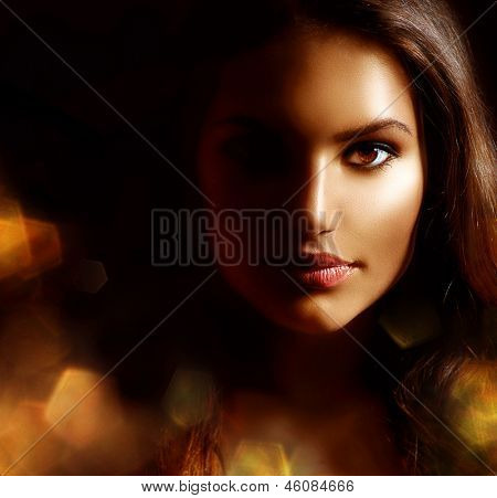 Beauty Girl Dark Portrait with Golden Sparks. Mysterious Woman Face. Darkness. Isolated on Black