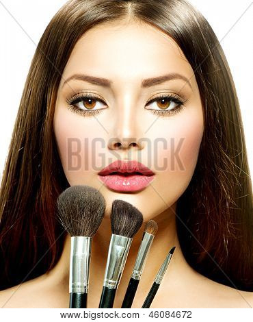 Beauty Girl with Makeup Brushes. Natural Make-up for Brunette Woman with Brown Eyes. Beautiful Face. Makeover. Perfect Skin. Applying Makeup