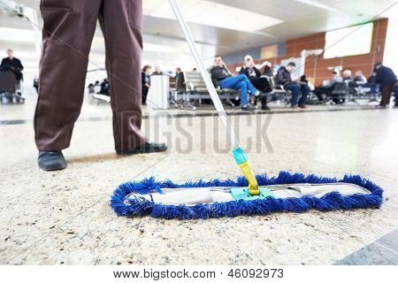 limpiador con trapeador y uniforme piso del hall del edificio de la empresa pública de limpieza