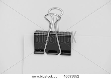 Black clerical clip for paper on white background