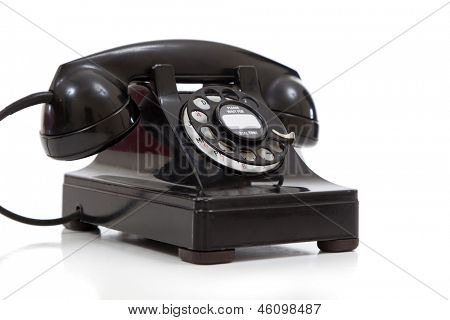 A vintage black rotary phone on a white background