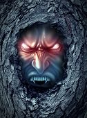 stock photo of demons  - Vampire zombie ghost with glowing evil eyes living inside a dark old haunted tree trunk as a halloween symbol of bad horror spirits haunting the living world as a monster demon looking for blood - JPG