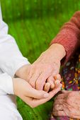 image of holding hands  - A young doctor holding the hand of an old woman  - JPG