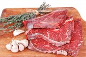stock photo of veal meat  - fresh raw beef meat fillet flesh with peppercorn and thyme ready to grill on wood figured old style board isolated over white background - JPG