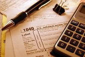 stock photo of death penalty  - IRS Tax Form with pen and calculator.
