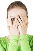 stock photo of peeking  - Shy or scared teenage girl peeking through covered face  - JPG