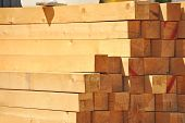 stock photo of log fence  - Fresh wooden beam stacked at construction site - JPG