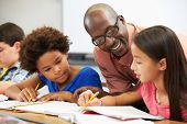 stock photo of pupils  - Teacher Helping Pupils Studying At Desks In Classroom - JPG