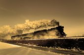 picture of loco  - Vintage steam train puffing through countryside during wintertime - JPG