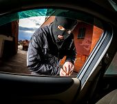 stock photo of mischief  - Robber and the car thief in a mask opens the door of the car and hijacks the car - JPG