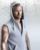 stock photo of hoods  - Sexy young fit man in hooded training vest against modern studio background - JPG