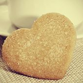 closeup of a heart-shaped shortbread biscuit and a porcelain cup with a retro effect