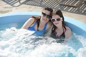 foto of hot-tub  - A mom and preteen daughter enjoying a dip in an outdoor hot tub on a sunny day - JPG