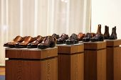 picture of neat  - Mens shoes in a store display arranged in neat rows on top of four wooden cabinets - JPG