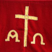 stock photo of ecclesiastical clothing  - Decorative symbolic gold needlework on a priests vestment or church cloth with a gold cross and religious icons on a red background - JPG