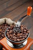 stock photo of wooden box from coffee mill  - coffee grinder with coffee beans on wooden table - JPG