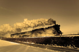 stock photo of loco  - Vintage steam train puffing through countryside during wintertime - JPG