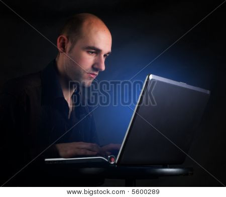 Businessman working at computer laptop late at night