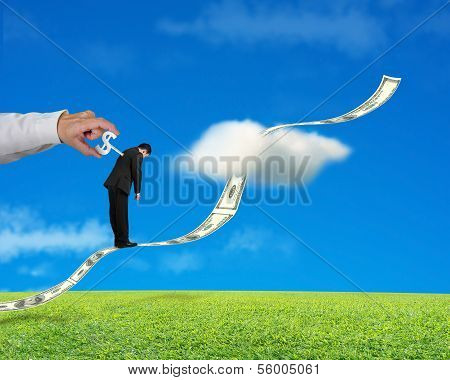 Businessman Standing On Growing Money Trend With Hand Winding