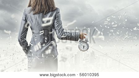 Back view of businesswoman holding alarm clock against city background