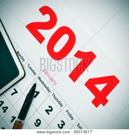 closeup of a desk with a notebook and a 2014 calendar