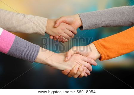 Handshakes on bright background