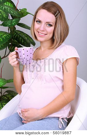 Young regnant woman sitting on armchair and holding cup at home