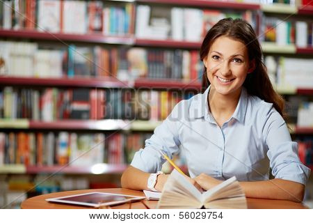 Portrait of pretty student looking at camera while working in college library