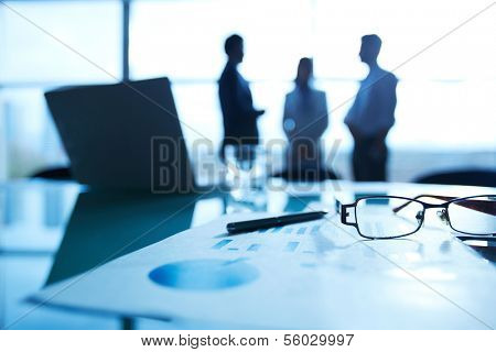 Close-up of business document, pen and eyeglasses at workplace on background of office workers interacting