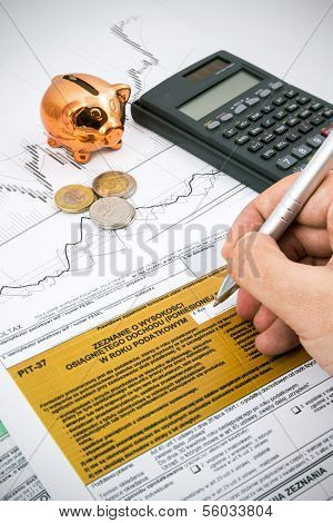 Man Hand Filling Pit-37 Income Tax Forms With Calculator And Coins
