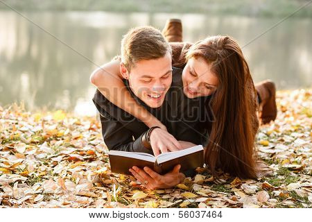 Young Couple Lying Down Reading