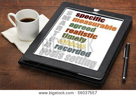 SMARTER (specific, measurable, agreed, realistic, timely, ethical,  recorded) goal setting concept  on a digital tablet computer with  espresso coffee