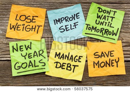 New Year goals or resolutions - handwriting on sticky notes against grained wood