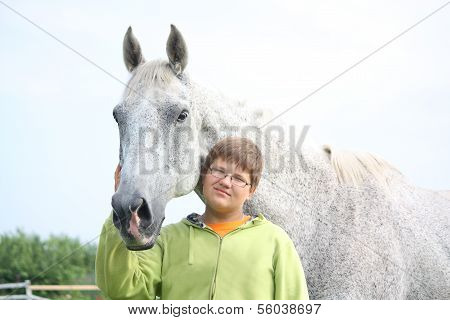 Happy Teenager Boy And White Horse At The Field