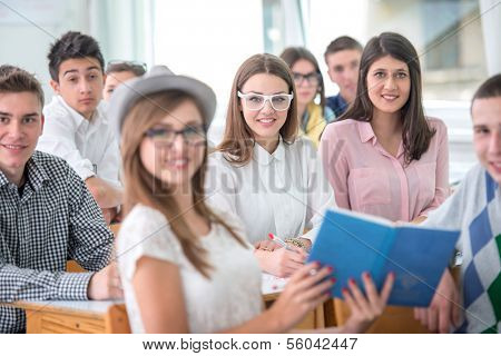 Sitting teenage pupils posing in schoolroom