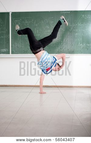 Playful boy performing breakdance in classroom