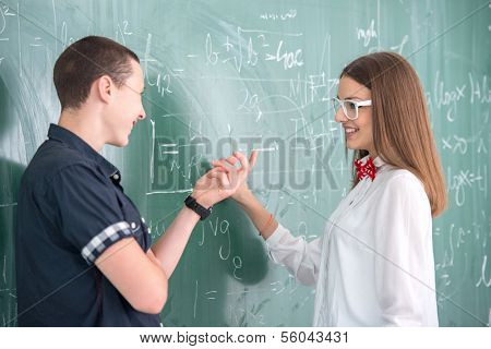 Two smiling highschool students standing on blackboard