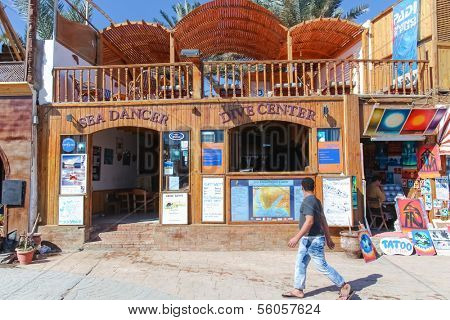 DAHAB, EGYPT - JANUARY 24, 2011: Man walking by the dive center on January 24, 2011 in Dahab, Egypt. Dahab has many diving centers because it is near the Blue Hole.