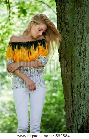 Blond Beauty In Yellow Blouse Posing Next To A Green Tree