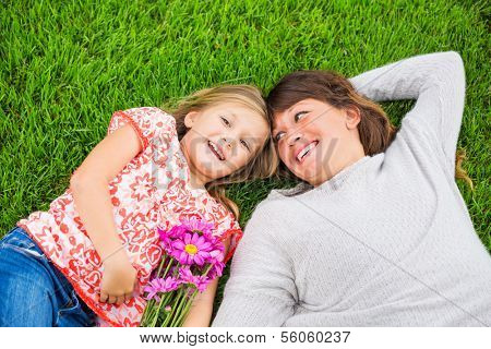 Beautiful mother and daughter lying together outside on grass, Special intimate moment