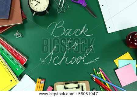 Back to School Supplies on Green Chalkboard Background