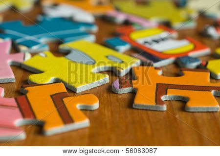 Children's Puzzle Scattered On A Wooden Table Close Up