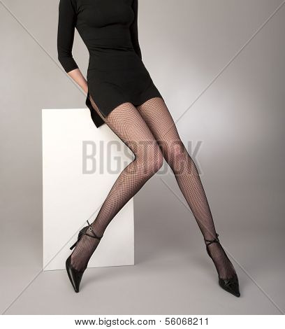 Shapely girls legs with black fishnet tights, fashion shoes and cocktail dress