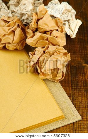Crumpled paper balls with notebook on table close up