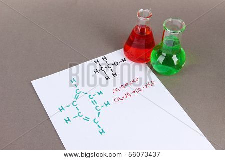 Test tubes with colorful liquids and formulas on grey background