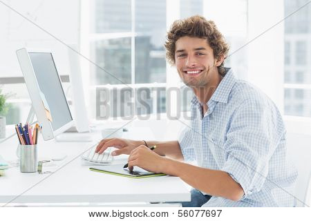 Side view portrait of a male artist drawing something on graphic tablet with pen