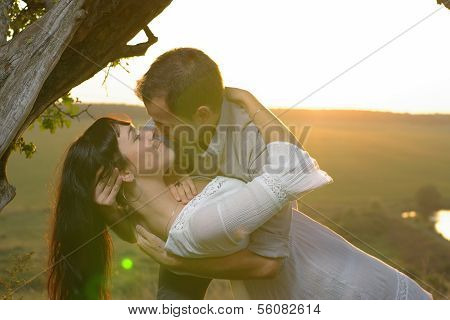 Two sweethearts kissing under tree
